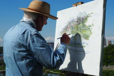 This shows an older man painting