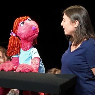 This shows the researcher and a pink, muppet like puppet