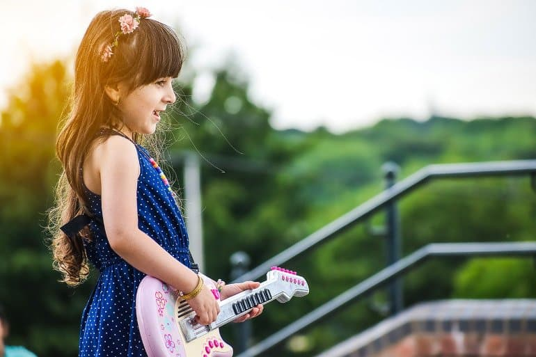 This shows a little girl singing and playing a toy guitar
