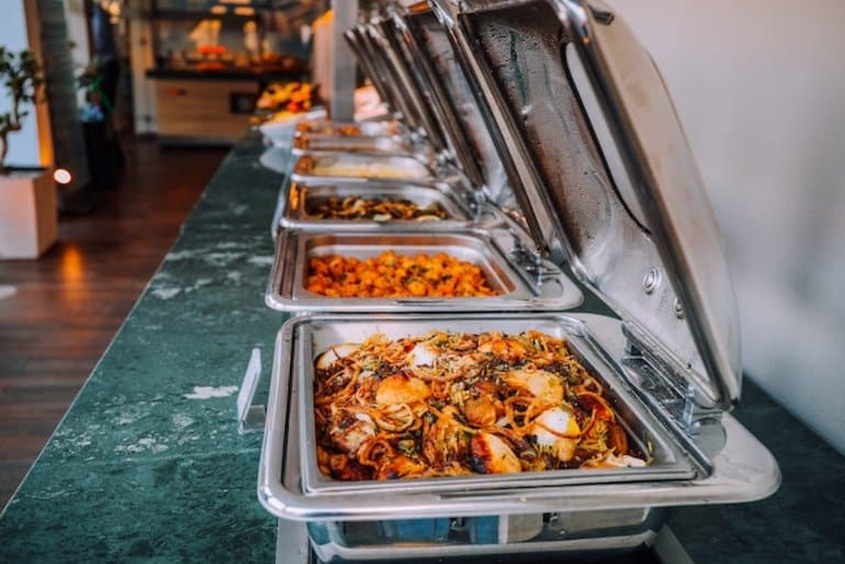 This shows different dishes on a buffet line
