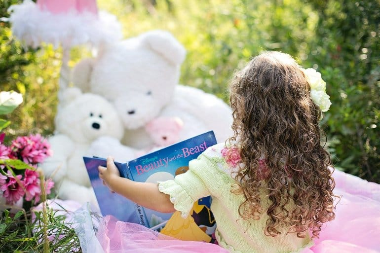 This shows a little girl reading to her toys