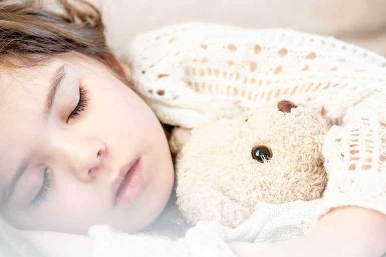This shows a little girl sleeping with her teddy bear