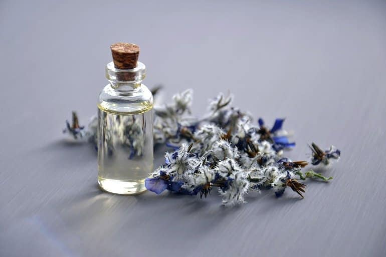 This shows a bottle of essential oil and lavender flowers