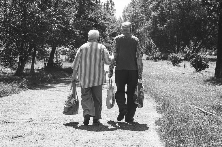 This shows an older couple walking with shopping bags
