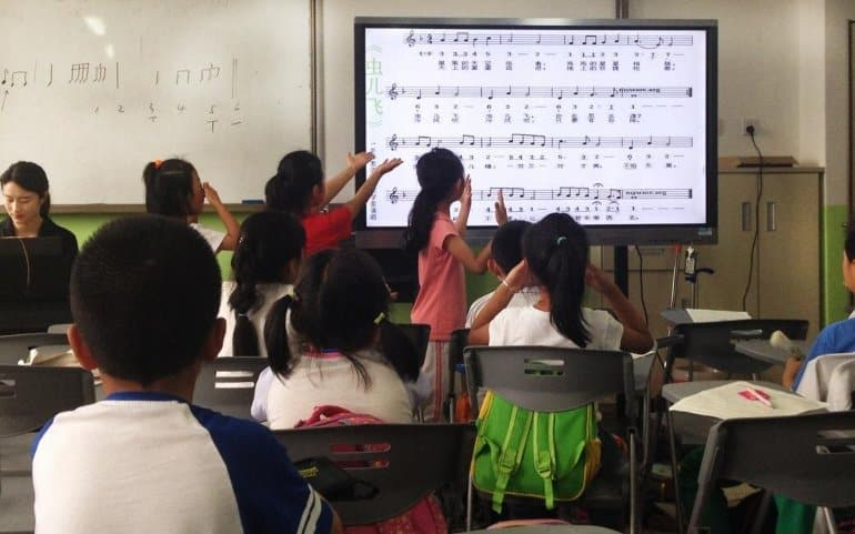This shows school children looking at sheet music on an overhead projector