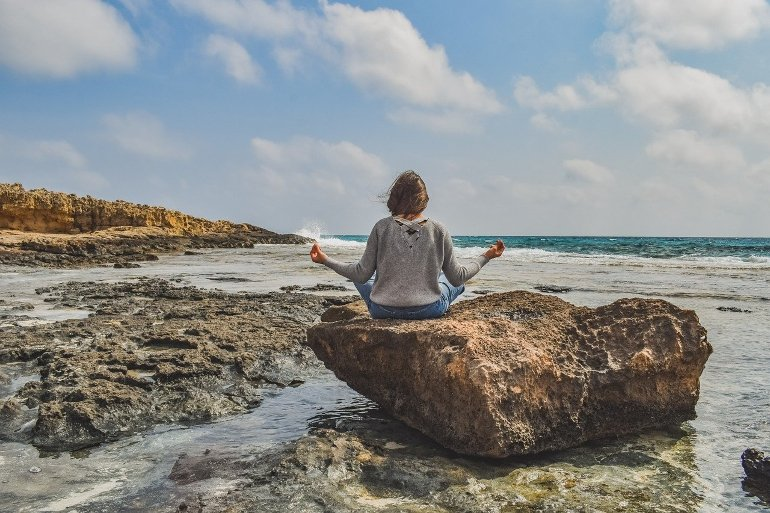 This shows a woman meditating on a rock at a beach