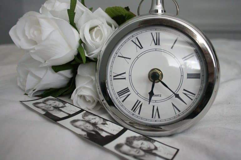 This shows some photographs, an alarm clock and white roses