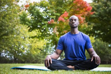 This shows a man meditating in a park
