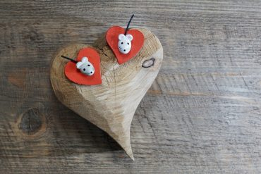 This shows two mouse toys on a wooden heart
