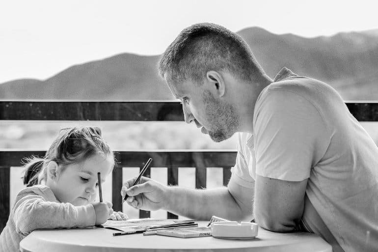 This shows a dad doing homework with his little girl