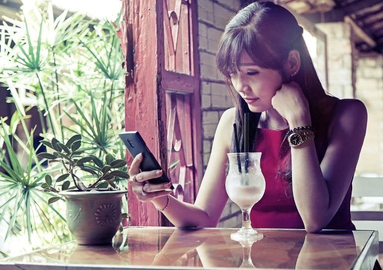 This shows a woman in expensive clothes looking at a cell phone