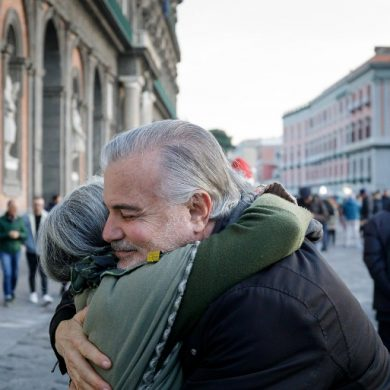 This shows old friends hugging in a street