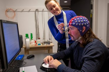 This shows the researcher putting an EEG cap on a study participant