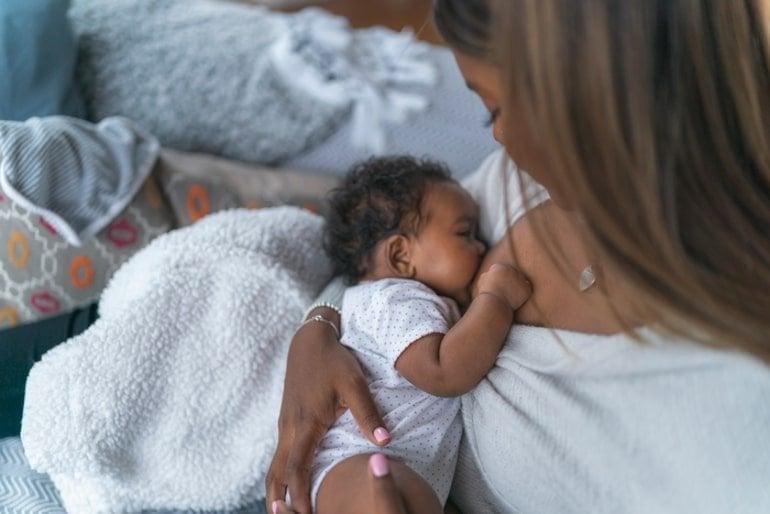 This shows a mom breastfeeding her newborn