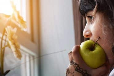 This shows a little girl eating an apple