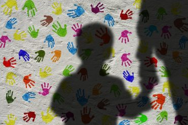 This shows a child's shadow and a wall covered in multi colored hand prints