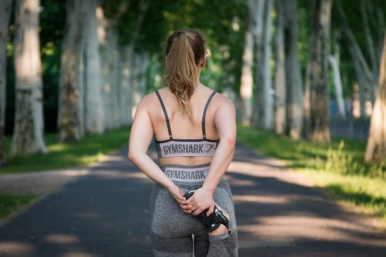 This shows a woman warming up for a run