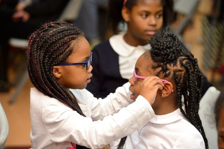 This shows a little girl helping her friend put on a pair of glasses