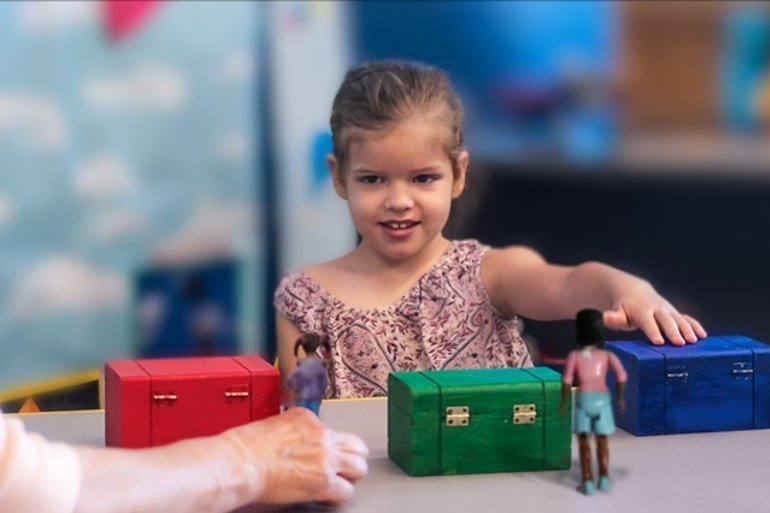 This shows a little girl with three different colored boxes