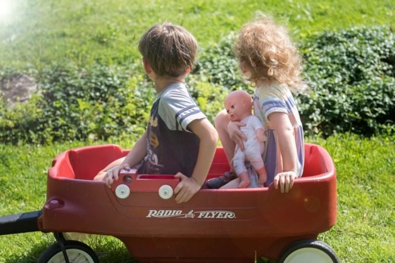 This shows children playing in a red pull wagon