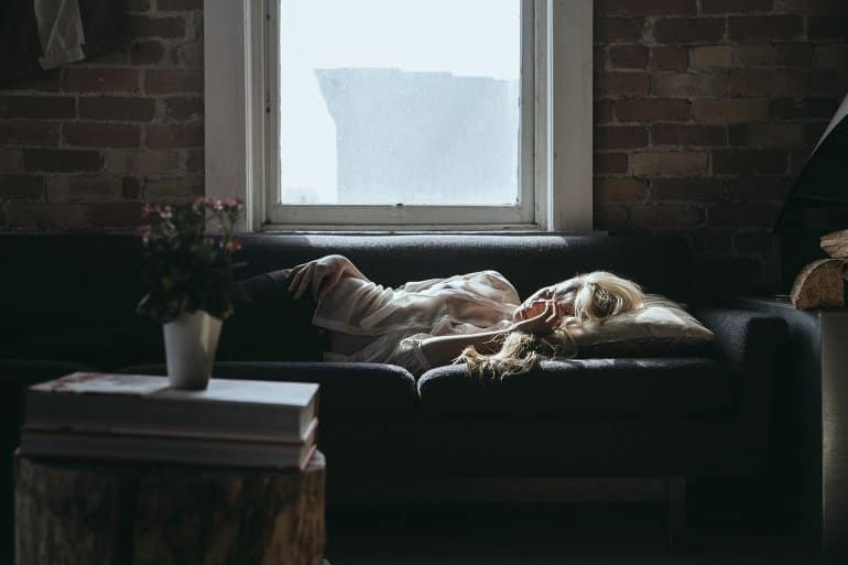 This shows a woman sleeping on a sofa