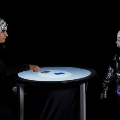 This shows a woman playing cards with a robot