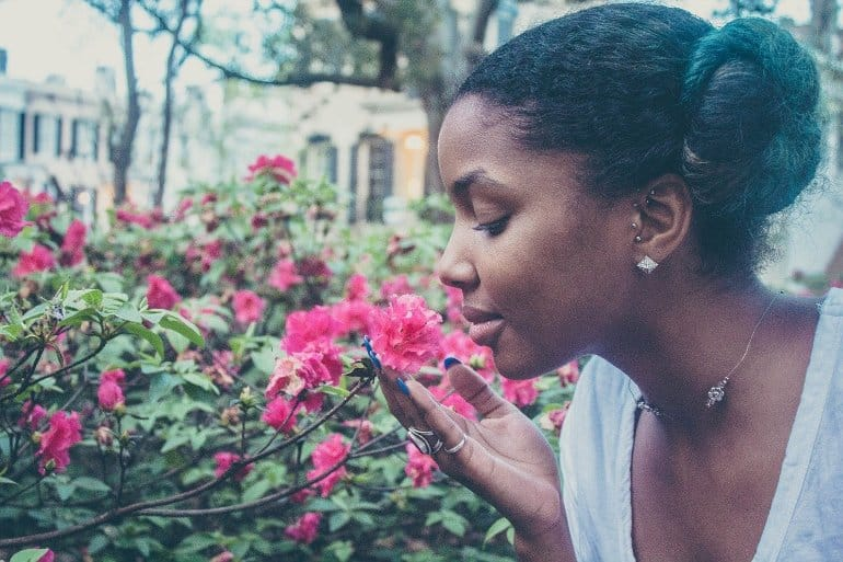 This shows a woman smelling flowers in a garden