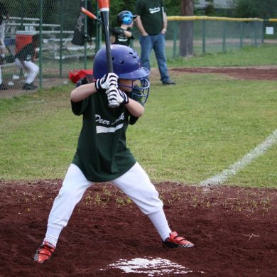 This shows a little boy playing baseball