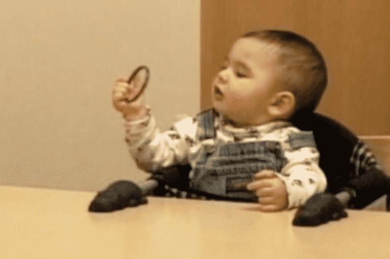 This shows a baby examining a circular object