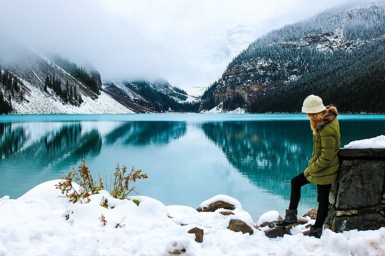 This shows a woman standing next to a lake on a snowy day