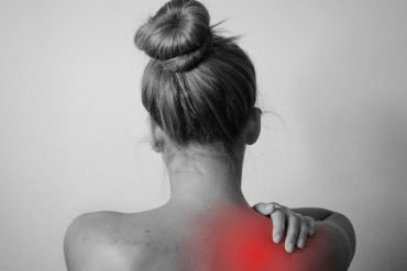 This shows a woman rubbing her shoulder as though it's in pain