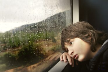 This shows a child looking out of a window