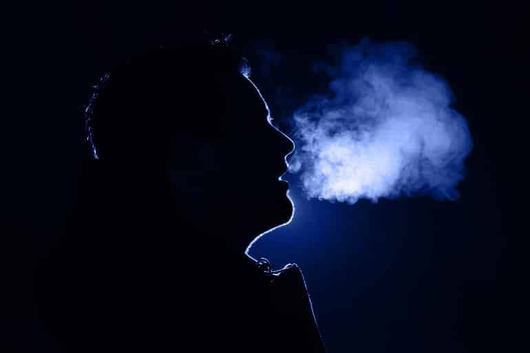 This shows a man breathing out a cloud of steam on a cold day