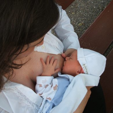 This shows a woman breastfeeding a newborn