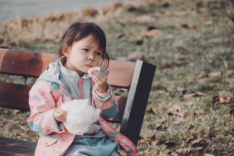 This shows a little girl eating cotton candy