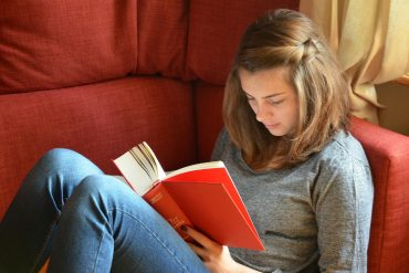 This shows a teenage girl reading a book