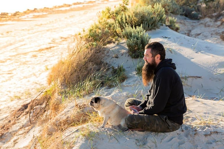 This shows a man sitting on a beach with his dog