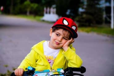 This shows a little boy looking sleepy. He's wearing an awesome Spiderman hat