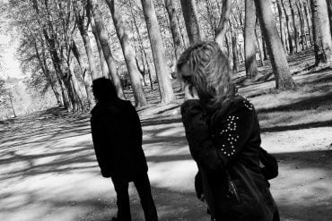 This shows a shadowy man walking away from an upset woman