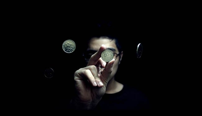 Picture of a person performing a magic trick with coins.