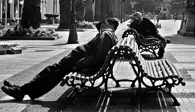 A man is asleep on a park bench.