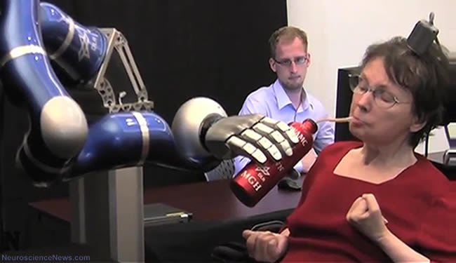 A woman is sitting in a chair with a small device on her head and is sipping a drink with a straw. The drink is being held by a robotic arm.
